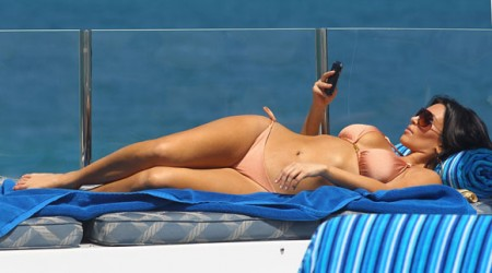 Kim Kardashina in a bikini with her Crackberry, er, Blackberry
