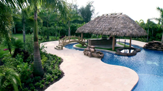 A massive swimming pool lagoon that has a lazy river as well as an island and tiki hut.